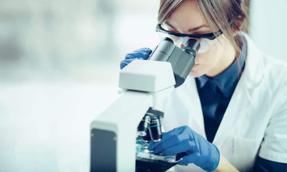 Woman looking at specimen through microscope