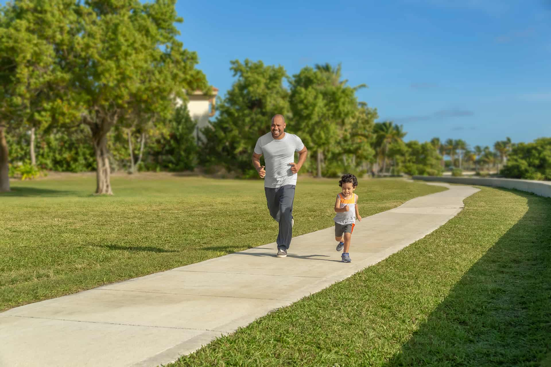 Father & son running at park during nice weather in Rosedale, CA