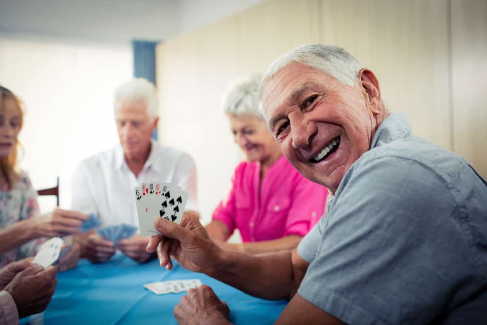 Senior citizens having fun playing cards.